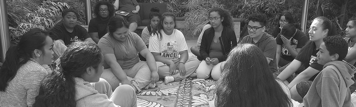 asian american and pacific islander students sitting in a circle on a blanket