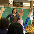 teacher standing in front of classroom where children are raising their hands